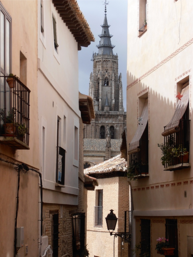 Shot through a narrow street bathed in sunlight, with the steeple towering gloomily in the background
