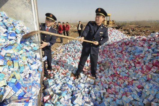 Chinese officials disposing of contaminated milk formula. [Photo Credit: Chinadivide.com]