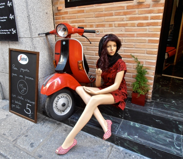 Half a red Vespa, guarded by Dolly