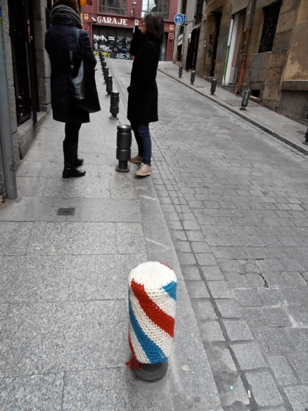 A bollard with a knitted cozy. Is it feeling the cold...? Were people stubbing their toes on it...? No. turns out, they (there were three of them)  were right outside a knitshop who hijacked them for advertising purposes.