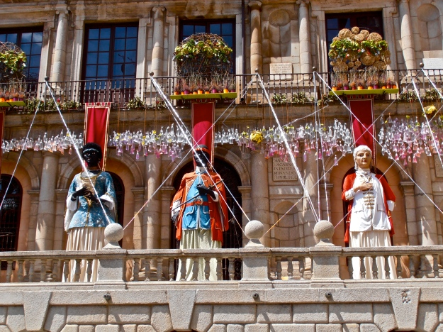 Never mind the giants lined up in front of the Town Hall - what's with the hundreds of bags filled with water dangling down from the balcony?!