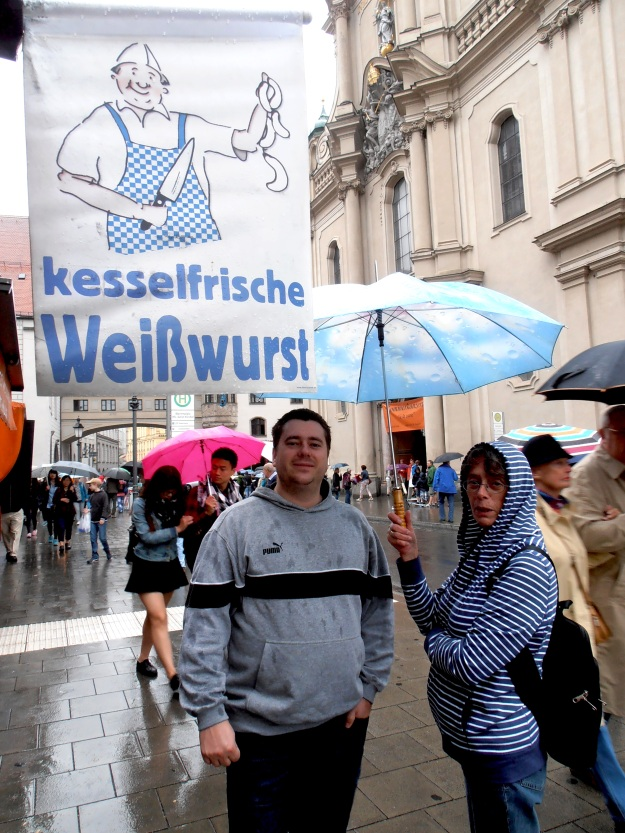 My brother and my mum beneath a sign in Munich advertising the most famous of Bavarian sausages: The Münchner Weißwurst.